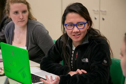 A student looks at her laptop as another woman looks on.