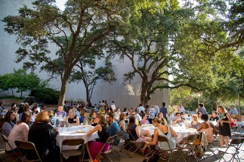 Faculty, staff, and students in the college enjoy a potluck outside the building.