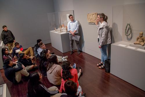 A young woman discusses a painting in the Blanton Museum with several youths.
