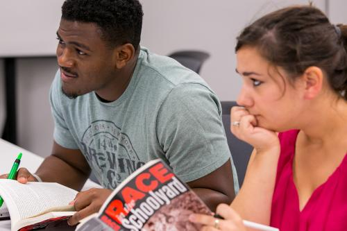 Two students examine their books, Race in the Classroom
