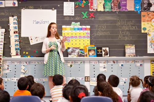 Teacher stands in front of a group of elementary students