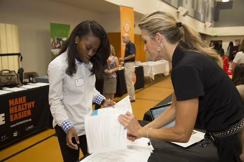 A recruiter talks to a student at a career fair.