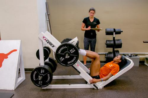 Student works on developing strength as a trainer looks on
