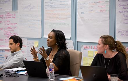 Three graduate students sit at a table in front of a wall full of large notes about leadership.