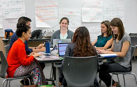 Graduate students listen as a classmate delivers a presentation.