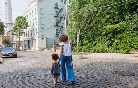 A mother and child walking down a city street