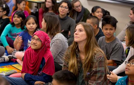 Two girls in focus among group of students listening intently