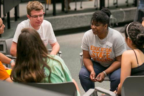 A black woman from the college's advising office talks with a diverse group of students.