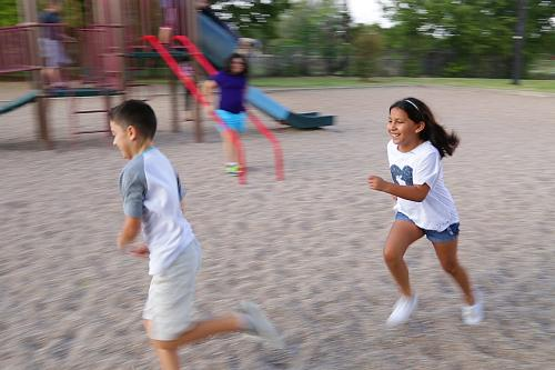 A diverse group of children run on a playground.