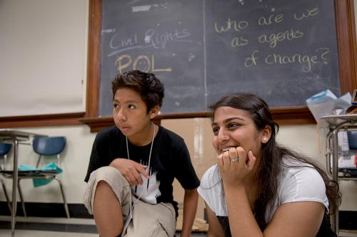 A young woman with long dark hair and a nose ring sits with a young boy in a classroom.