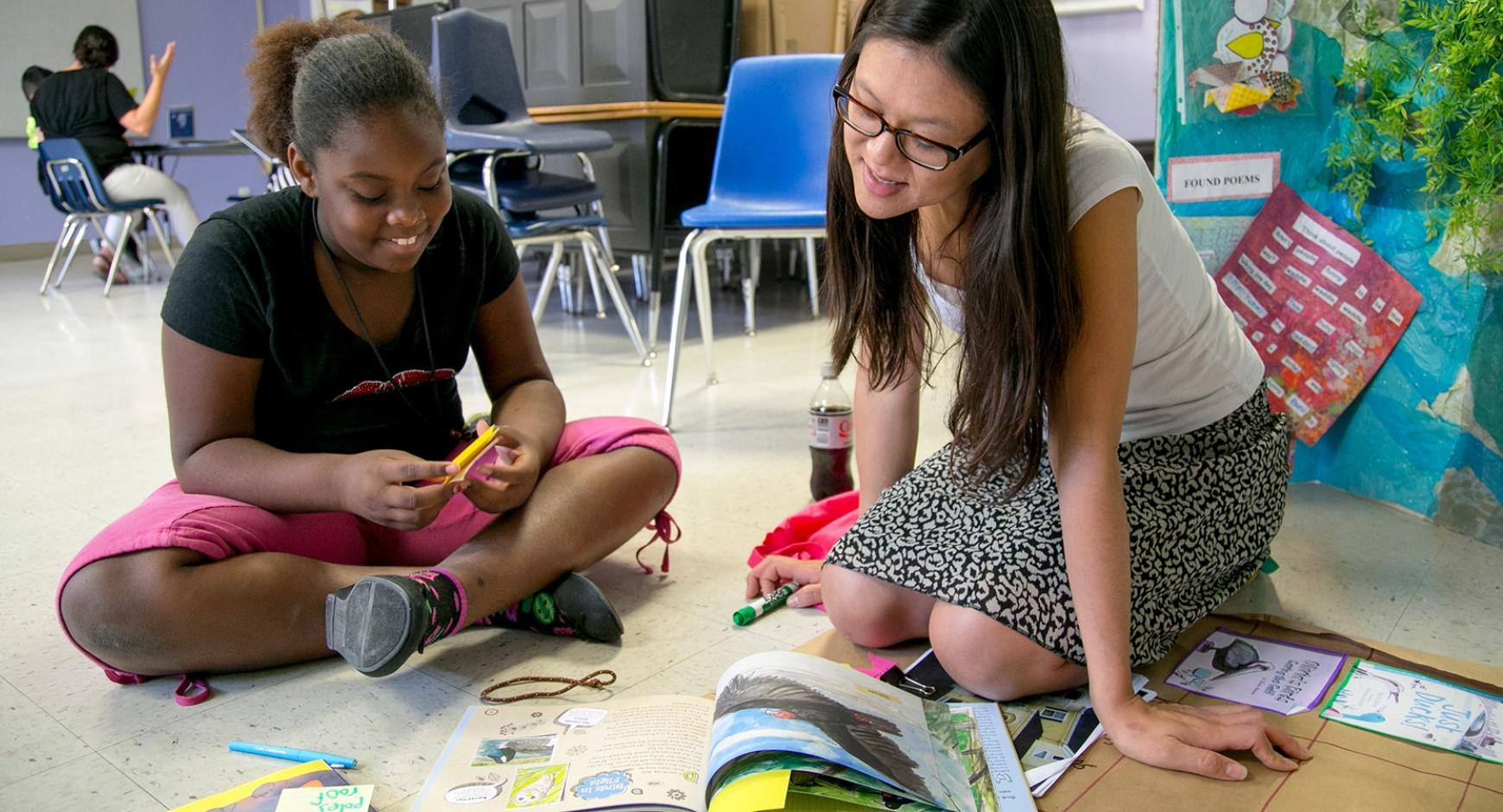 A young woman works with a girl on reading comprehension.