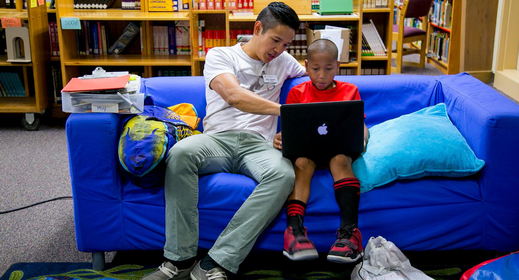 A young man shows a boy how to use a laptop.