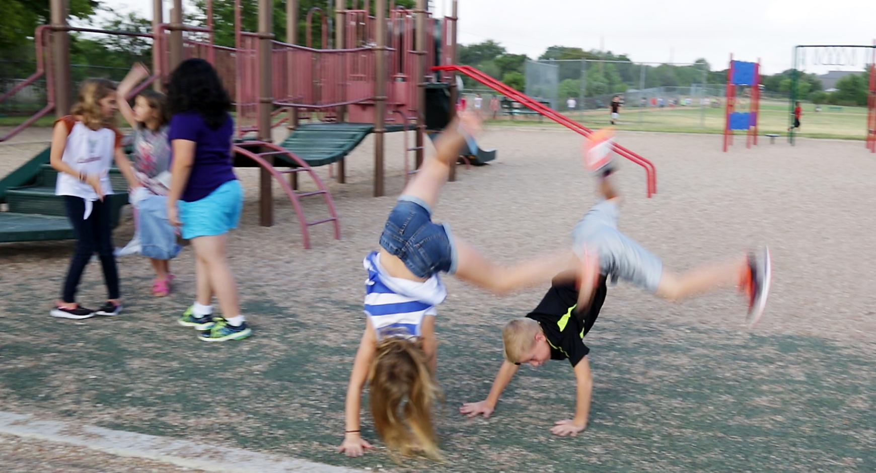 A boy and a girl turn cartwheels while other children run on a playground.