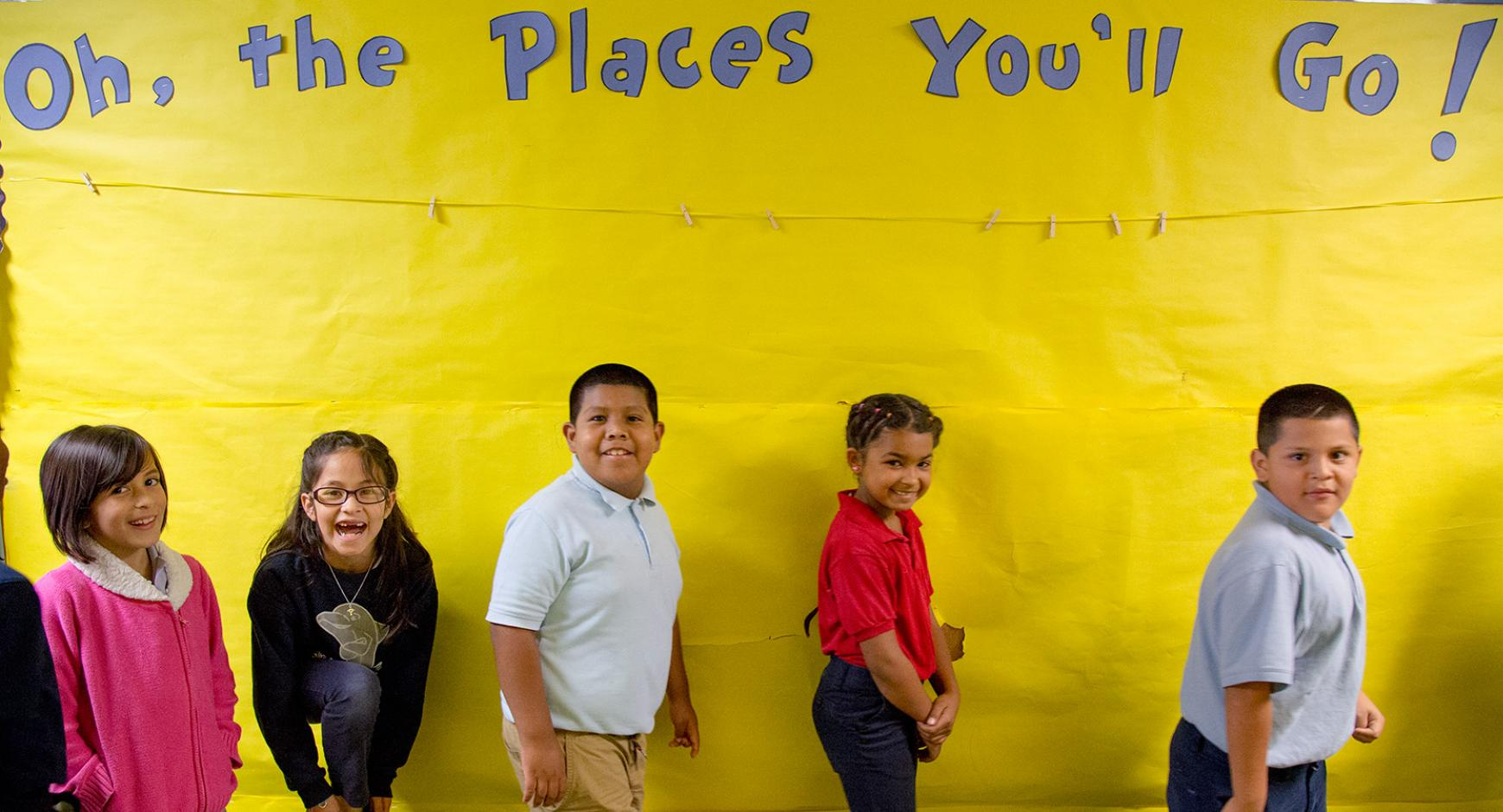 "A group of elementary students stand in front of a sign reading, ""Oh, the Places You'll Go!"""