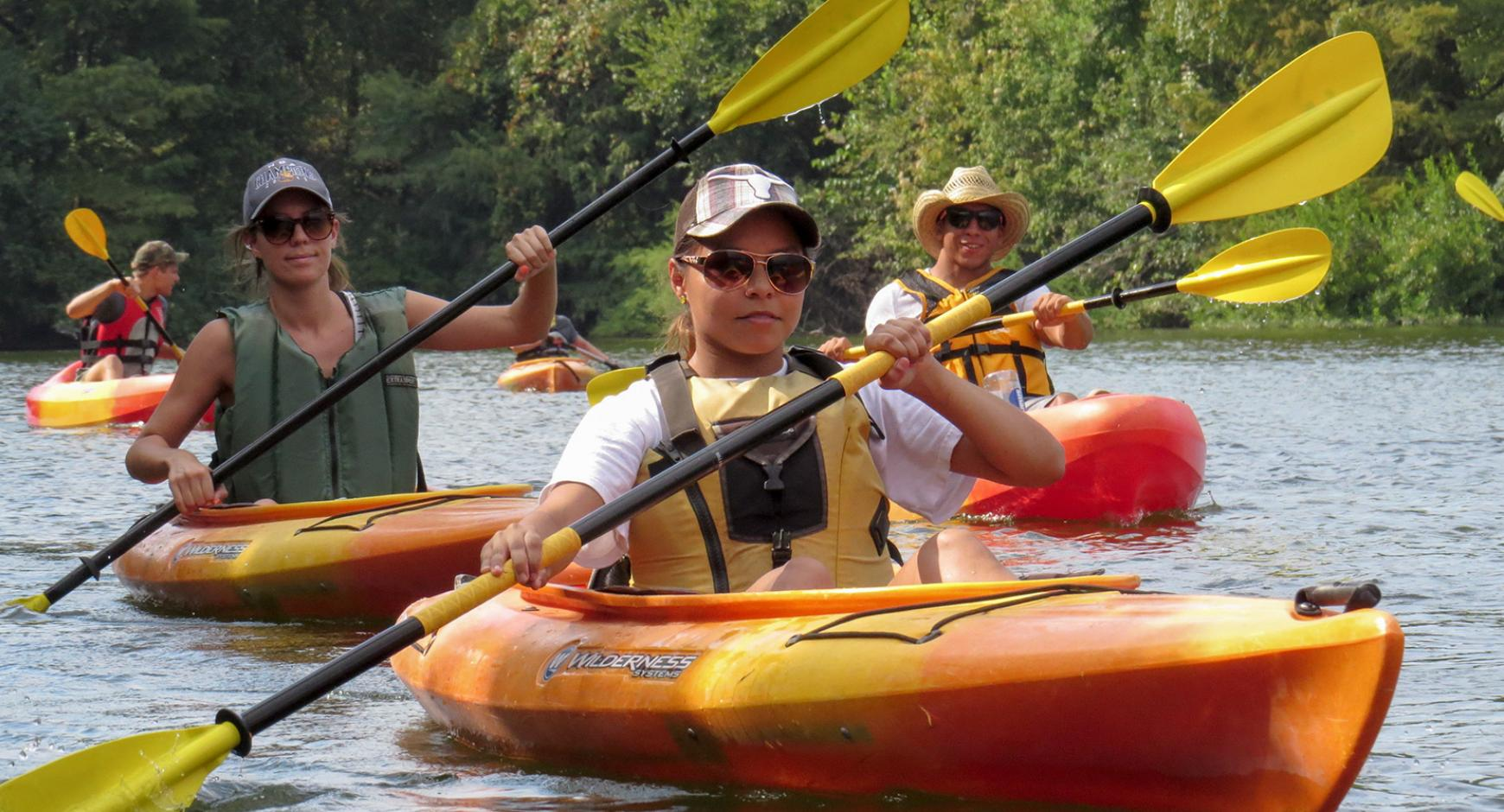Several students learn how to kayak.