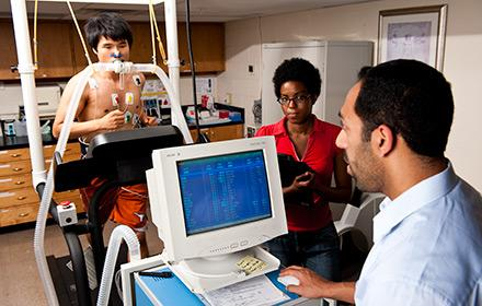 Students measure the lung capacity of an athlete running on a treadmill.