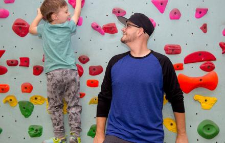 Matt Bowers and his son on a rock climbing wall