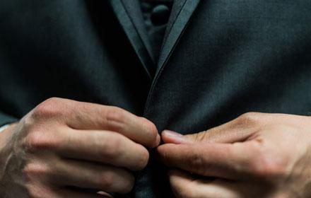 Hands buttoning a jacket