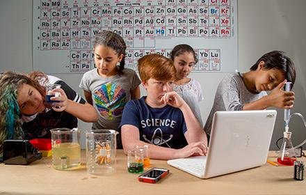 A group of middle school students collaborate on a science project.