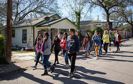 A group of students walk through an Austin community.