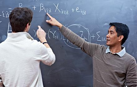 Two young men work on a math problem at a chalkboard.