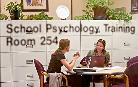 """Two women sit at a table behind a glass door that reads """"School Psychology Training."""""""