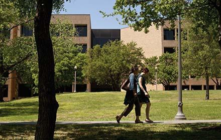 Two students walk across the lawn in front of the Sánchez building.