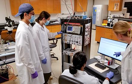 A diverse group of students wearing lab coats stands around computer equipment