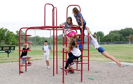Children get exercise playing on a jungle gym.