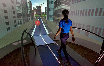 A young woman walks on a treadmill while looking at a large screen depicting a city scape.