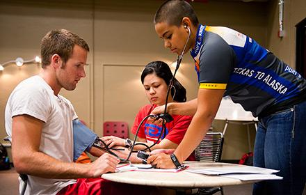 Students check an athlete's blood pressure.