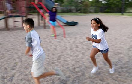 Two children run on a playground while another looks on from a jungle gym.