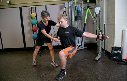 A trainer works with an athlete to correct his form while exercising.