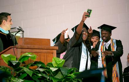 Graduating students taking a selfie on stage near podium