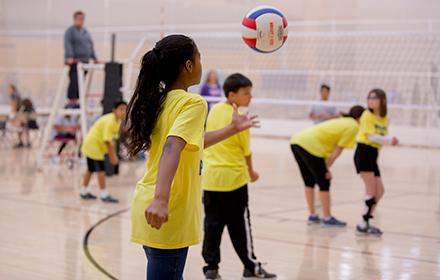 A girl prepares to serve a volleyball.