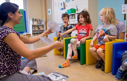 A young woman works with several young children in a daycare setting.