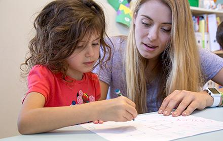 A young woman provides guidance to a girl working on a problem.
