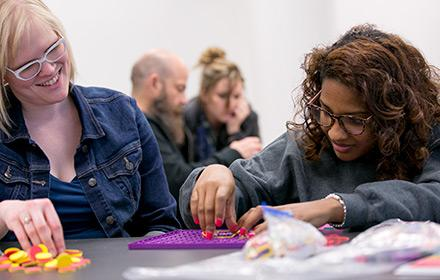 Two women work on a puzzle during a workshop on multicultural special education
