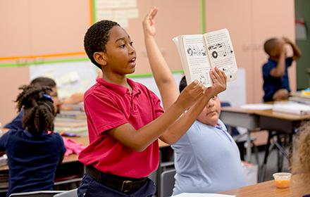 A young boy with short, curly hair and dark skin holds up a book in a classroom.