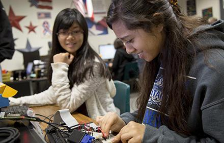 A teenaged girl works on a raspberry pi while another girl looks on.