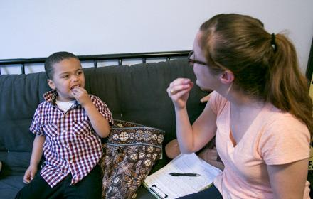 A young woman works with an autistic boy while sitting on a sofa.