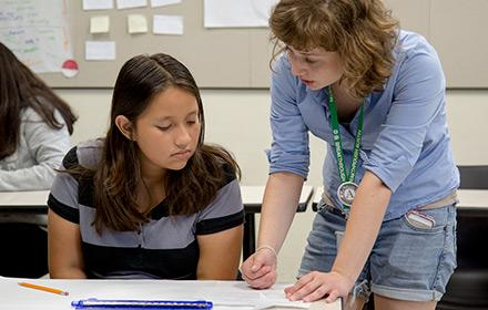 A student teacher works with a middle school student.