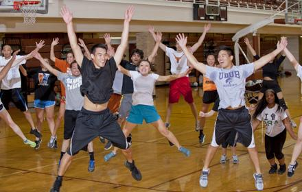 A group of students jump for exercise in a gym.