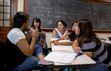 A diverse group of teenage girls listen to dark-skinned student teacher during a discussion session.