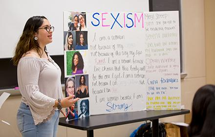A young latina woman reviews a poster on sexism in front of a class.