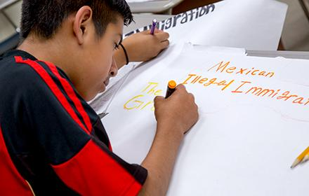 A Latino teenager prepares a poster for class