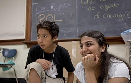 A young boy and a student teacher look on as someone else speaks