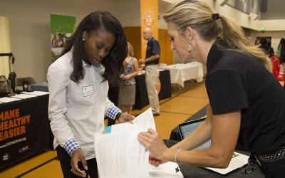 A woman assists a student with her resume.