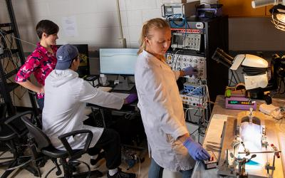 Assistant professor Audrey Stone works with students in a lab