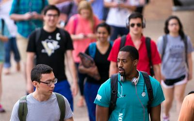 A diverse group of students walk across campus.